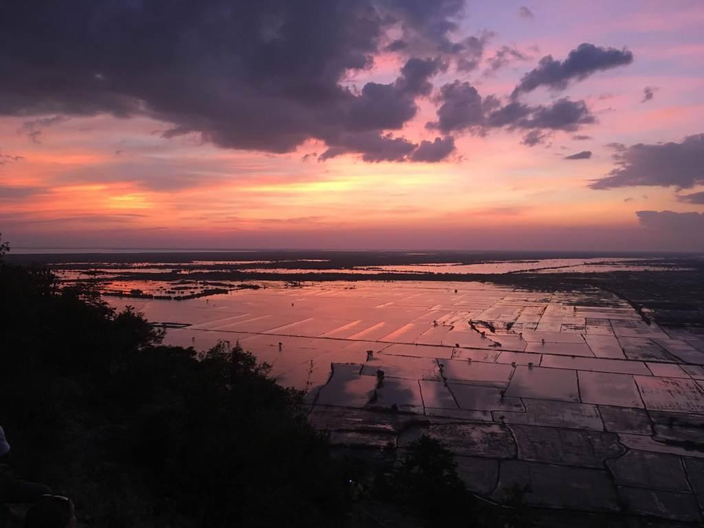 The sun sets over the rice fields near Phnom Krom mountain